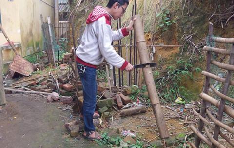 A boy cuts firewood.