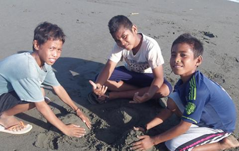 Three boys play in the sand.
