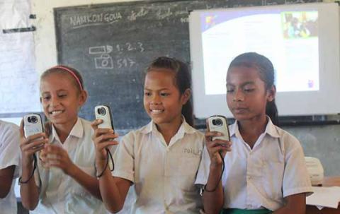 Three girls hold cameras.