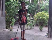 I child sweeps outside a house.