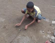 A boy plays marbles.